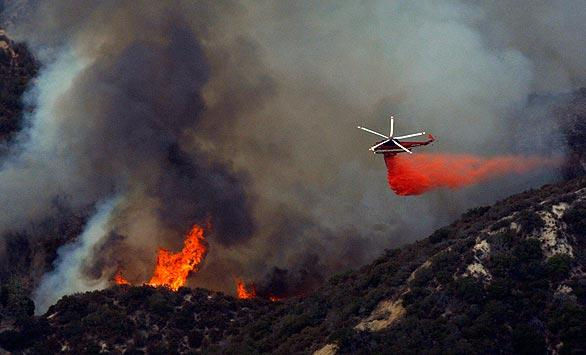A helicopter drops fire retardant on a part of the Station fire burning close to homes in Tujunga's Blanchard Canyon.