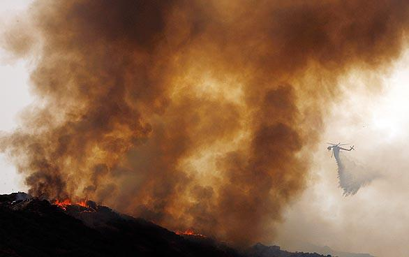 A helicopter drops water on a burning ridgeline in Tujunga. Cooler, cloudier and more humid weather has slowed the progress of the Station fire, which continues to burn out of control in the mountains north of Los Angeles.