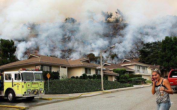 A resident talks on her cellphone as a smoky hillside looms behind homes on Boston Avenue in La Crescenta on Tuesday.