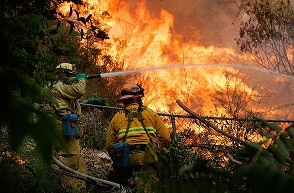 Firefighters douse brush as flames burn in a canyon, moving away from a home on Arnell Place in La Crescenta on Tuesday.