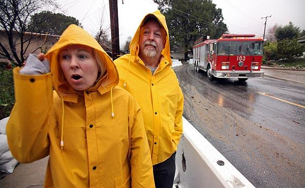 Starr and Rick Frazier react as they see their neighbors evacuating their Ocean View Boulevard home in the foothills above La Cañada Flintridge. The Fraziers refused to evacuate, saying they will ride out the storm in their home even though their neighborhood is under a mandatory evacuation order.
