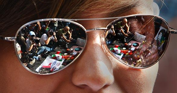 Photographers are reflected in the glasses of one of the fans encircling Michael Jackson's star on Hollywood Boulevard on the morning after Jackson died.