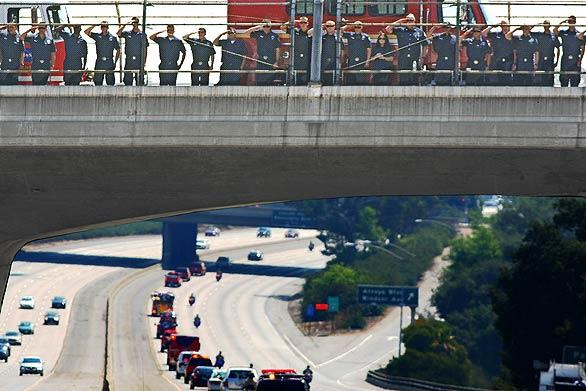 Firefighters, top, stand at attention and salute the procession along the 210 Freeway escorting the casket of Los Angeles County Fire Capt. Ted Hall, who was killed in the Station fire.