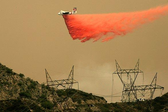 A plane makes a fire retardant drop on the Station fire on ridges along Little Tujunga Road.