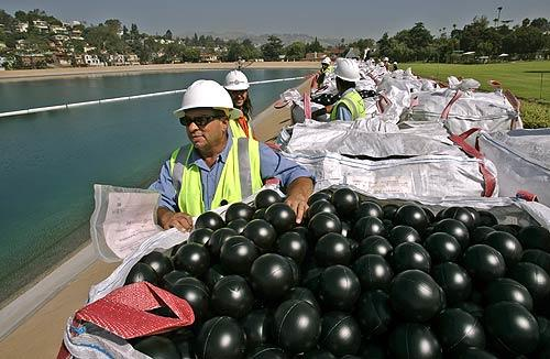 DWP worker Manuel Martinez waits for the signal to empty out bales of black balls into the Ivanhoe Reservoir in Los Angeles. The Department of Water and Power released about 400,000 4-inch black plastic balls as the first installment of approximately 3 million balls that will form a floating cover over the reservoir.