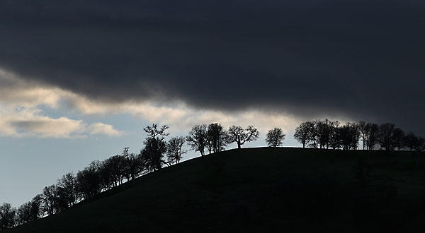 Dark clouds move over a tree-dotted ridgeline in the proposed conservation area.