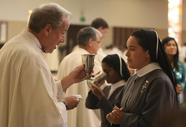 Father Christopher Smith distributes Holy Communion  during the ordination to the priesthood of four men at St. Columban Church in Garden Grove. Smith will take the top post at the new Christ Cathedral.