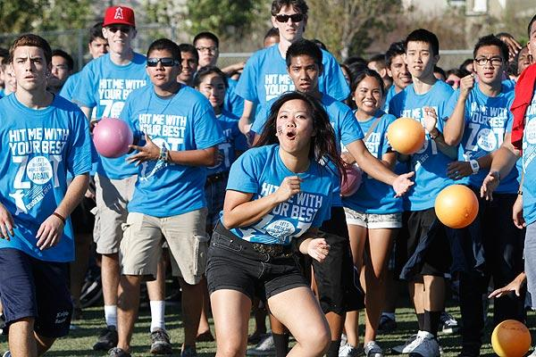 UC Irvine senior Kathy La reacts to a hit after leading the charge of the blue team in a game that set the world record for most people playing dodgeball: 6,084 players.