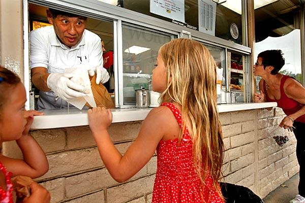 Jim Nakano, owner of the the Donut Man in Glendora, hands doughnuts to Jadeyn, left, and Faith Ehmke. Nakano, 71, is a third-generation Japanese American who has a developed a loyal following with his seasonal strawberry- and peach-filled creations. Oh, and the maple bars and Bavarian creams are good too. <br>