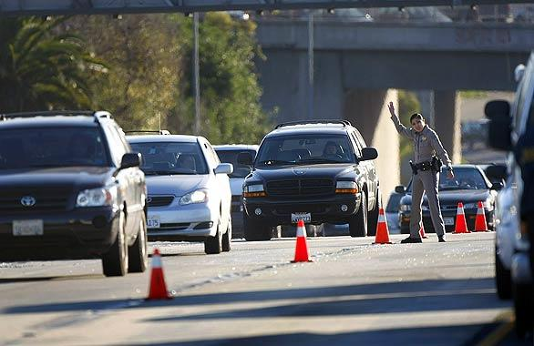 "A California Highway Patrol officer directs westbound traffic, which was affected by the investigation of the fatal head-on crash on the eastbound Santa Monica Freeway near National Boulevard..<br> <br> Story: <a href=""http://latimesblogs.latimes.com/lanow/2009/01/freeway-crash.html"">Eastbound 10 Freeway closed by collision involving possible wrong-way driver</a>"