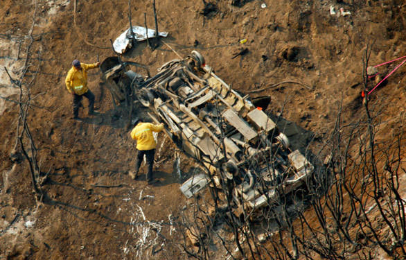 L.A. County fire investigators survey the vehicle that went off the road and fell nearly 1,000 feet down a steep ravine near Mt. Gleason in Angeles National Forest, killing county firefighters Tedmund Hall, 47, and Arnaldo Quinones, 34.