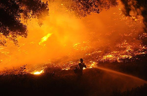 A U.S. Forest Service firefighter battles flames in La Crescenta.