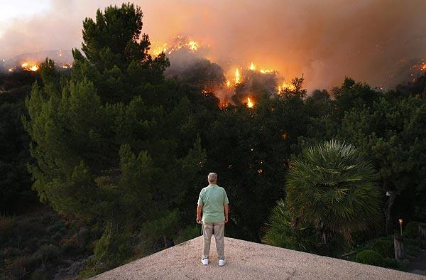 Roger Daniels, a La Crescenta resident since 1964, watches a backfire from the edge of his roof.