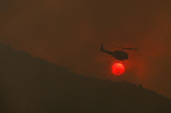 A helicopter finishes a water drop and flies over the setting sun over the town of  Acton.