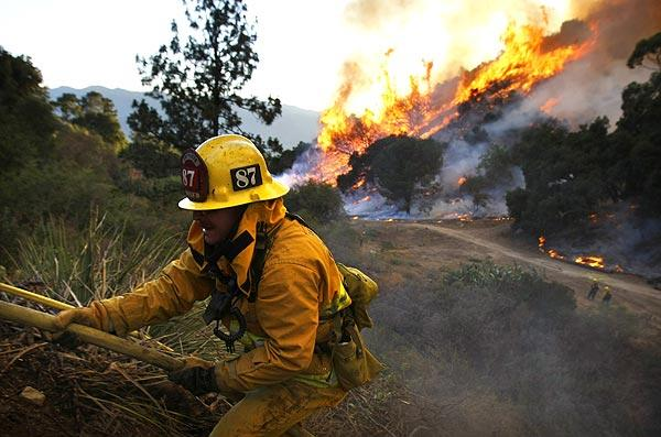 A firefighter climbs up a hose after a backfire is lit in La Crescenta.