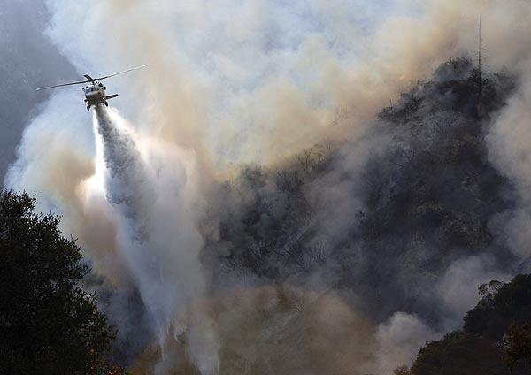 A helicopter makes a drop over the fire burning in the Angeles National Forest north of La Ca?ada Flintridge.