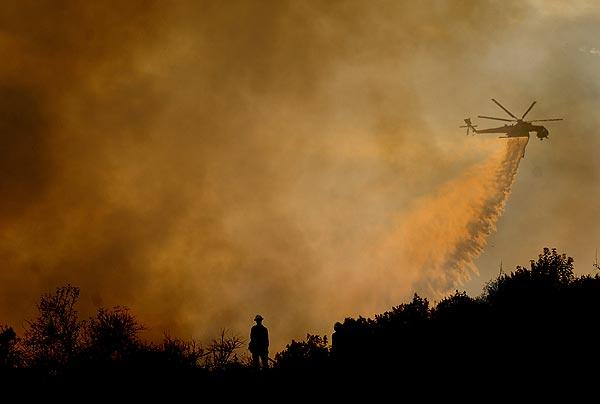 A U.S. Forest Service firefighter monitors the Station fire as a helicopter makes a water drop on a ridge along Angeles Crest Highway in La Ca?ada Flintridge.