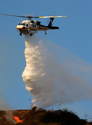 A Los Angeles County fire helicopter makes a water drop to help extinguish hillside flames as Los Angeles firefighters battle a blaze in the Sepulveda Pass.