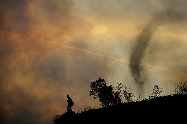 A U.S. Forest Service firefighter monitors the Station fire as smoke spins behind him on a ridge along Angeles Crest Highway in La Ca?ada Flintridge.