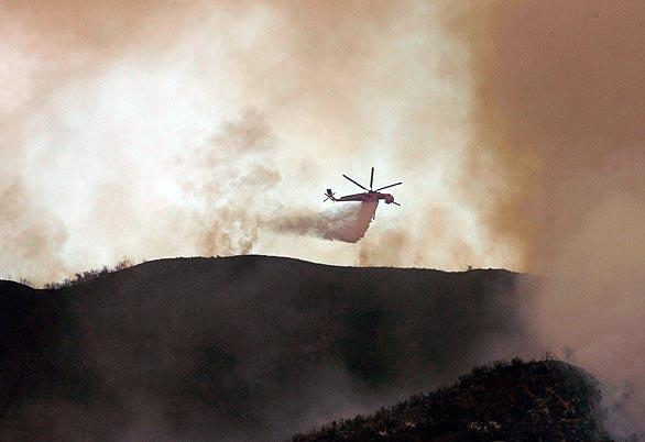 A helicopter drops water on the Morris fire.