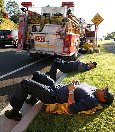 Fire crews from Los Angeles County Fire rest while they wait for their assignment in Rancho Palos Verdes.