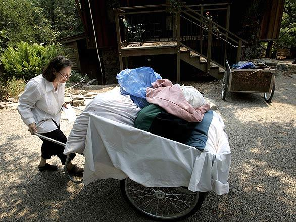 Sonja Gardenswartz moves linens from a guest cottage to a truck to be taken away as fire approaches the Tassajara Zen Mountain Center.