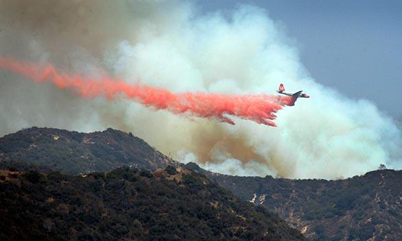 An airplane drops fire retardant Thursday afternoon in the Angeles National Forest in a view from Foothill Boulevard in La Cresenta. With temperatures hovering near 100 degrees, firefighters are trying to contain flames racing through dry brush in the forest north of the foothill community of La Canada Flintridge.