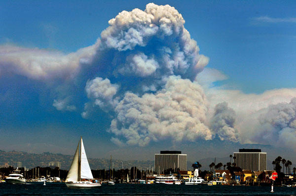 A sailboat makes its way through the harbor in Marina del Rey against a backdrop of smoke from the Station fire.