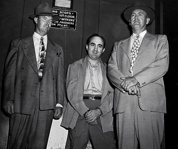 Mickey Cohen, flanked by Deputy U.S. Marshals Charles Ross and Earl Baugher, in a jail elevator, July 1951.