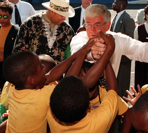 Republican vice presidential nominee Jack Kemp shakes hands with youths at Challengers Boys and Girls Club in South Los Angeles during a 1996 campaign stop.