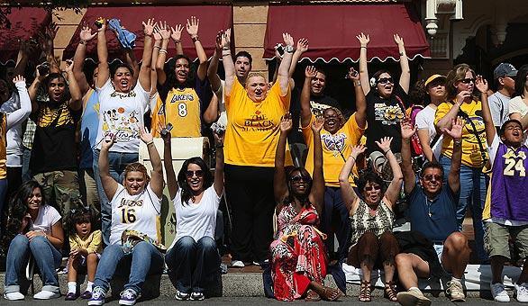 Laker fans do the wave as they wait to see Kobe Bryant parade down Main Street in Disneyland.