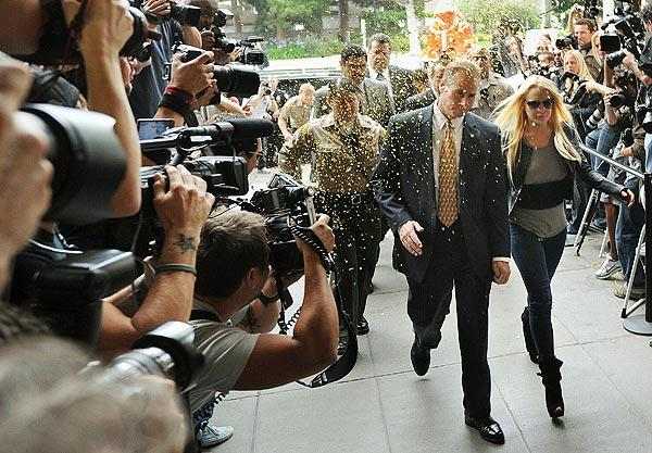 Lindsay Lohan walks through confetti as she arrives at the courthouse.  After Lohan's court appearance, a couple of unmarked cars pulled up to the side of the courthouse to take her to jail. Paparazzi crowded around the vehicles to snap pictures through the tinted windows