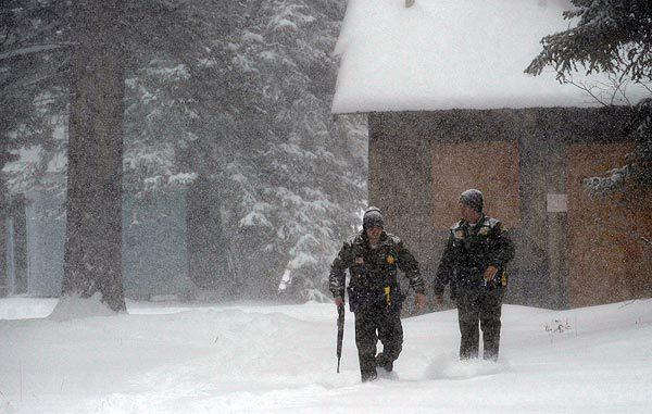 San Bernardino County sheriff's deputies trudge through snowfall near Switzerland Drive as they continue to look for murder suspect Christopher Dorner in Big Bear Lake on Friday.