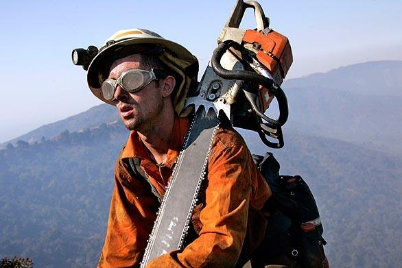 Jonathan Powers climbs back up Newman Point after cutting fire line in the area along Glendora Mountain Road,  southeast of Highway 39.