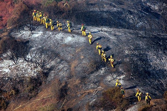 A Cal Fire crew from San Diego walks over a charred area on their way to mop up hot spots in the area southeast of Highway 39.