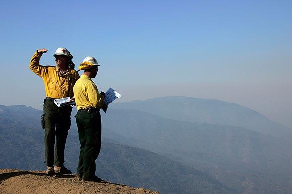 Workers from Gila Hotshots in New Mexico survey the fire area before sending a crew down a steep hill at Newman Point to cut fire line.