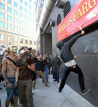 An Occupy Oakland protester jumps to hit the Wells Fargo sign at 12th and Broadway with a hammer as fellow protesters look on.