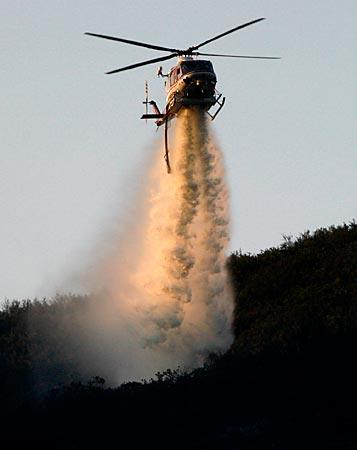 At daybreak, an Orange County Fire Authority helicopter drops water on a blaze off Ortega Highway in the Cleveland National Forest about 12 miles east of San Juan Capistrano.  The fire was reported shortly after midnight and burned about 25 acres before it was fully contained.