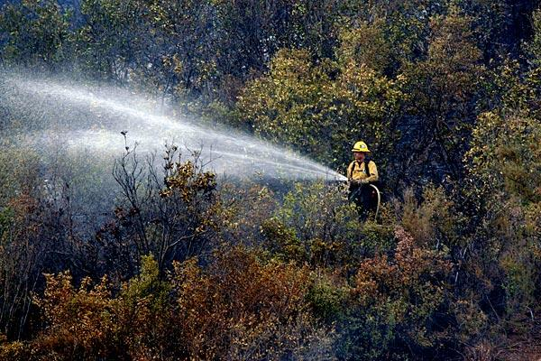 A U.S. Forest Service firefighter attacks a hot spot in the Cleveland National Forest.