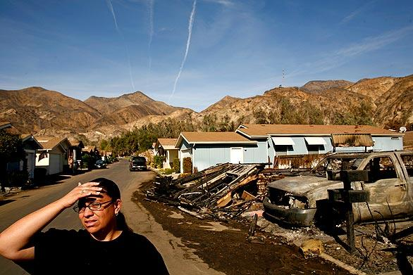 Katrina Vieane walks along her street in Oakridge Mobile Home Park, surveying the damage to her neighborhood in Sylmar's Sayre fire. Her house was not destroyed, but she can't stay there because of damage to the park's infrastructure. She and her children have moved to a nearby apartment.