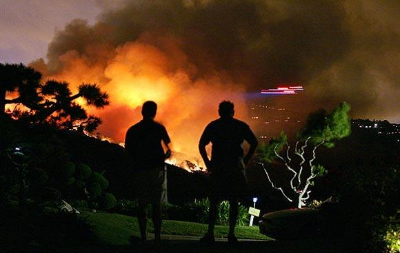 Residents of Cartier Drive in Rancho Palos Verdes watch as a helicopter, right, makes a water run at a brush fire in the  Portuguese Bend area.
