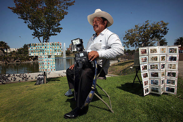 "Javier Prado sits in his folding chair waiting for customers at MacArthur Park. Photographers such as Prado, with their old-fashioned Polaroid cameras, have been fixtures in the area for nearly 40 years. <br> <a href=""http://www.latimes.com/news/local/la-me-photographers-20100708,0,2950325.story""><u>See full story</u></a>"