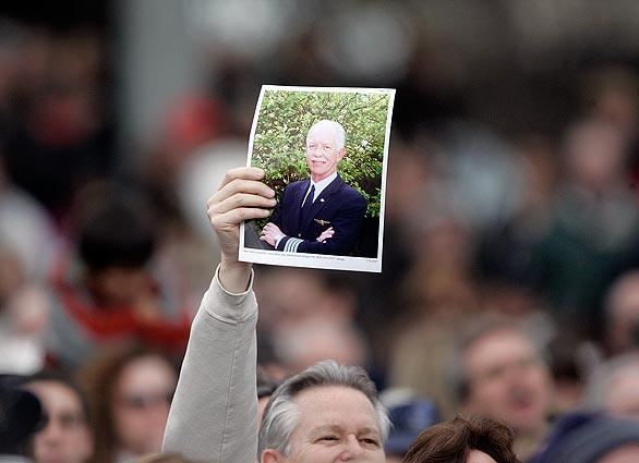 A man holds a photograph of the Danville, Calif., hometown hero, US Airways Capt. Chesley Sullenberger.