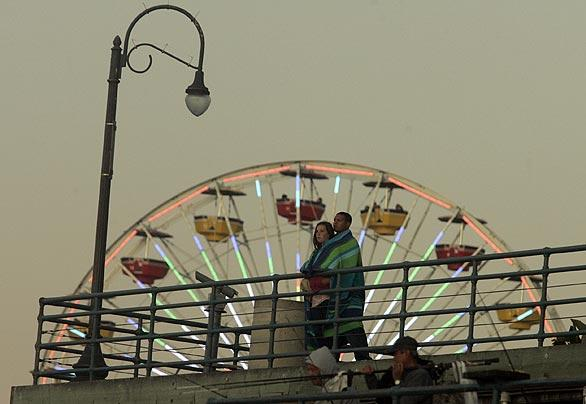 A couple look out from the Santa Monica Pier as sunset approaches. In honor of its centennial, the pier will host a fireworks show Sept. 9, the first over Santa Monica Bay since 1991.