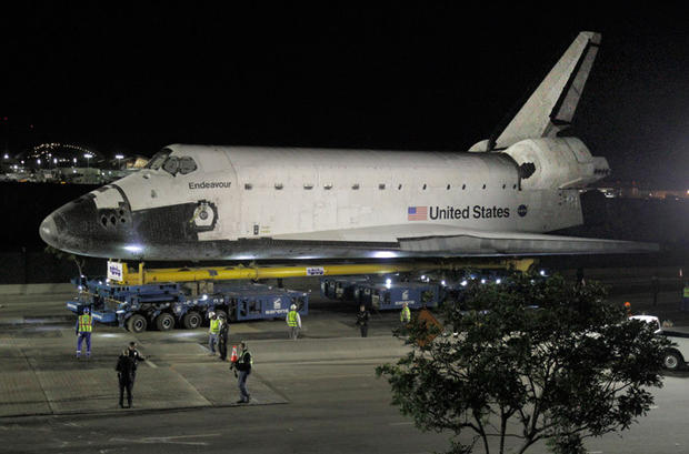 Workers move around the space shuttle Endeavour as it is transported from LAX to its new home at the California Science Center.