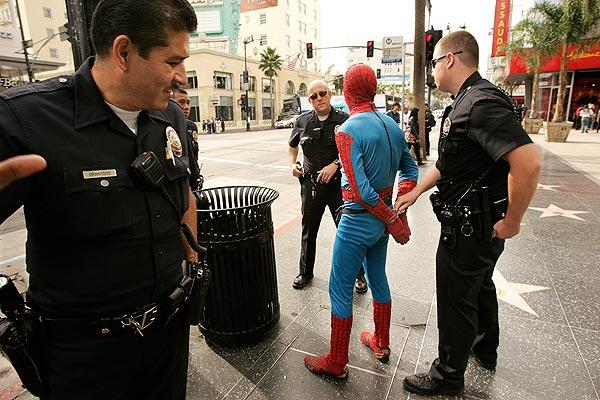 LAPD officers arrest a man in a Spider-Man outfit after he allegedly assaulted a man on the 6800 block of Hollywood Boulevard in Hollywood on Wednesday. The victim refused to press charges, but the Spider-Man character was still booked on outstanding misdemeanor charges.