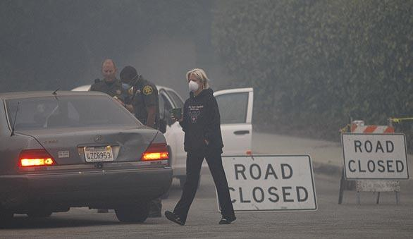 La Ca?ada Flintridge resident Patti Maloof sports a mask at a checkpoint on Ocean View Boulevard as she keeps a close eye on the burning hills near her home.