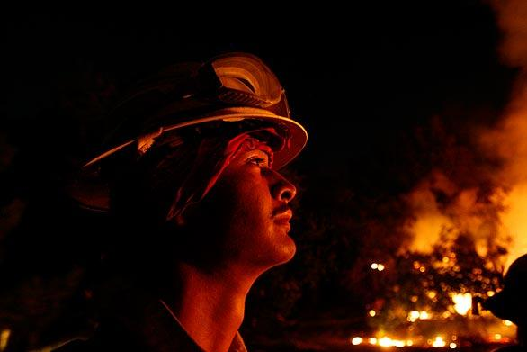 Matthew Cleaver, 20, of Arizona keeps an eye on a backfire near the corner of Rosemont Avenue and Rockdell Street in La Cresenta. The Forest Service set the backfire to help protect homes on the ridge.