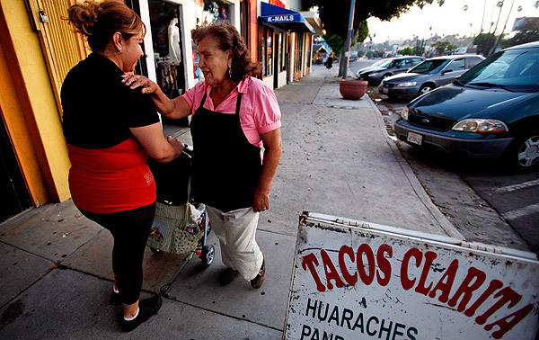 Clarita Trujillo, right, greets Alma Rodriguez in front of Tacos Clarita in El Sereno. Trujillo is very friendly and greets most passersby with a smile and conversation. <br>