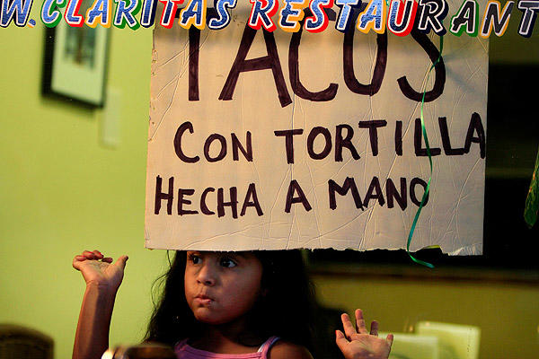 Kenia Camacho, 5, peeks out the window at Tacos Clarita. <br>